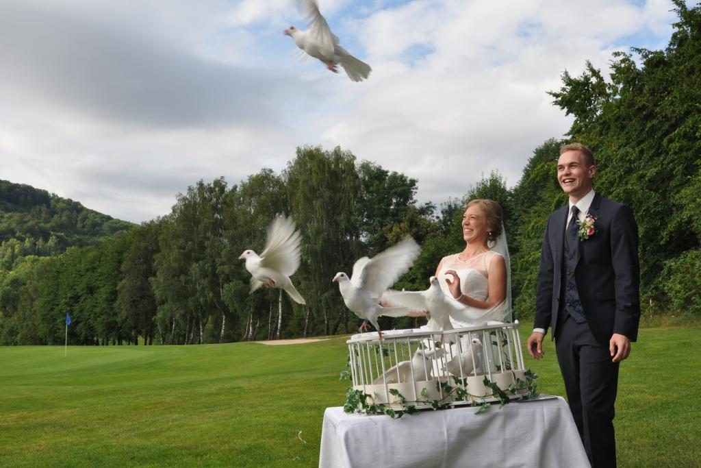 Ein Brautpaar lässt Tauben auf einer Lichtung fliegen