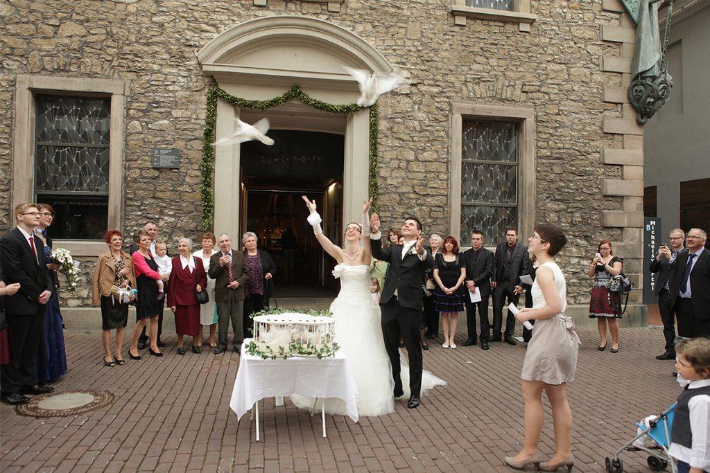 Tauben starten vor einer Hochzeitskirche
