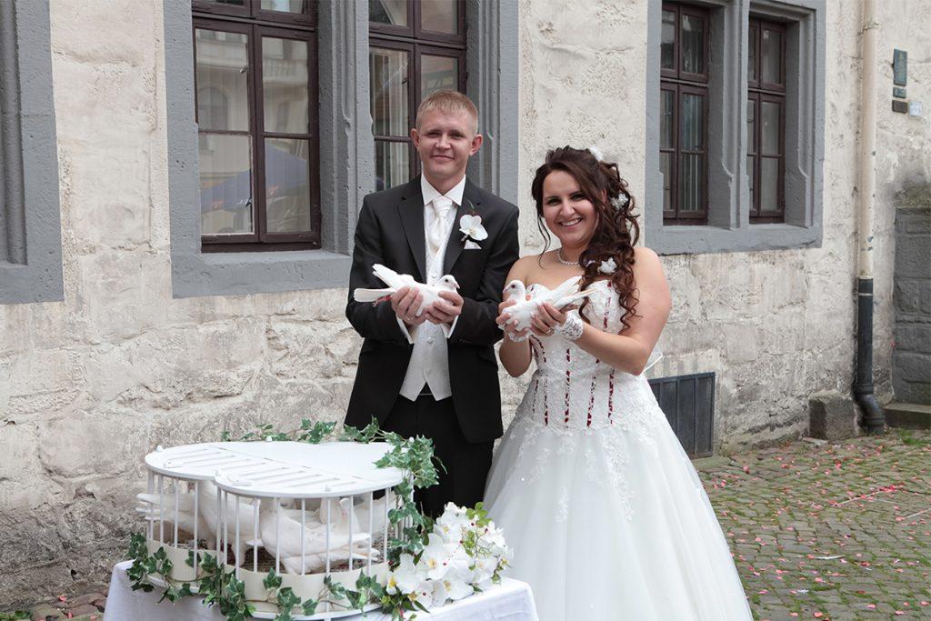 Ein Brautpaar präsentiert seine Hochzeitstauben