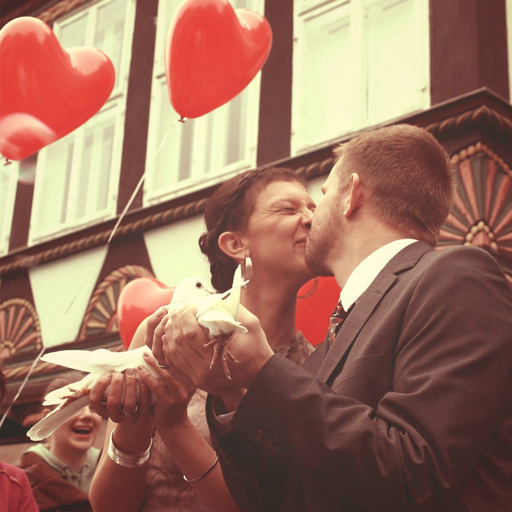 Ein Küssendes Brautpaar mit Tauben
